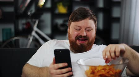 упитанность : Fat man smiles while he reads something in his smartphone and eats potato chips