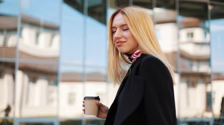 портфель : Young transgender woman walks with a cup of coffee along the mirror wall outside