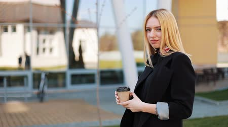 imbibe : Pretty young blonde woman stands with a cup of coffee before a mirror wall outside Stock Footage