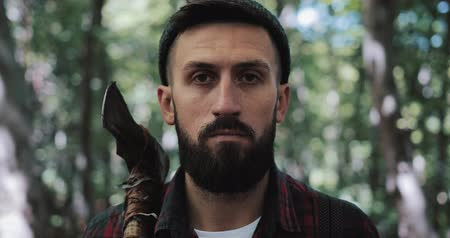 surroundings : Portrait of serious confident lumberjack, adult bearded man holding a big axe and looking into the camera in outdoors surrounding. He stands against the background of the forest