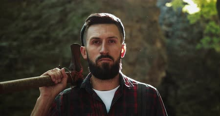 топор : Portrait of serious confident lumberjack, adult bearded man holding a big axe and looking into the camera in outdoors surrounding. He stands against the background of the forest