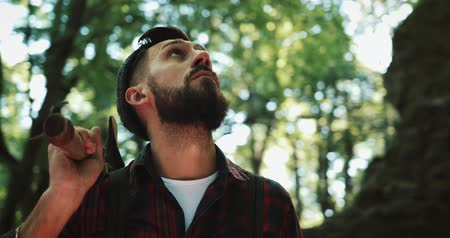 топор : Lumberjack standing with his ax in the woods, looking around. Portrait of handsome bearded man with ax