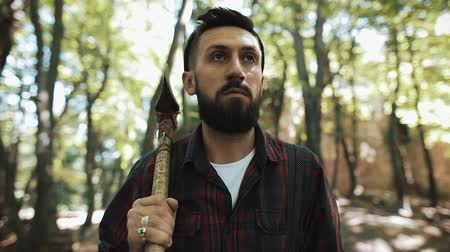 one man only : Walking bearded lumberjack with axe. Man in a cap walks through the woods in search of the tree