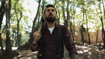 adults only : Walking bearded lumberjack with axe. Man in a cap walks through the woods in search of the tree