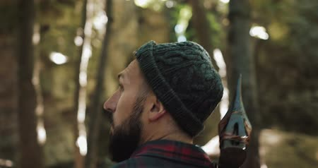 oyma : Walking bearded lumberjack with axe. Man in a cap walks through the woods in search of the tree. View behind the back Stok Video
