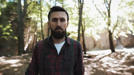 hickory : Portrait of handsome bearded man walking in the forest. A lumberjack looking into the camera Stock Footage