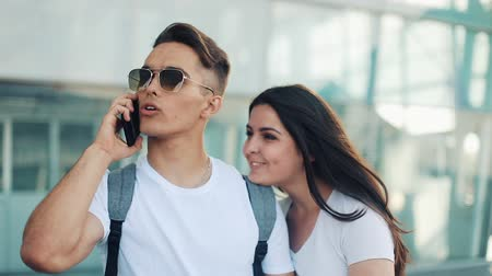 nevető : Attractive young couple standing near the airport. A man calls a taxi or call the delivery service. Communication, technology, smartphone concept