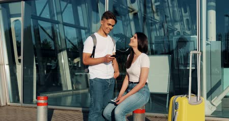 pas : Happy couple in love using smartphone, listen to music and talk to each other. Young married couple having fun in waiting for a flight at the airport Dostupné videozáznamy
