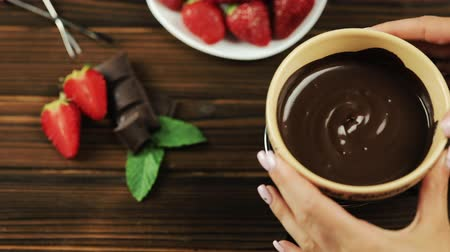 biała czekolada : The chefs hands put the fondue on the table. Fondue with chocolate strawberries on a wooden background
