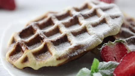 opłatek : Portion of Belgian Waffles with fresh Strawberries on the plate. The chefs hand sprinkling dessert sugar powder