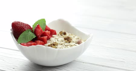 owies : The mans hand puts a plate of muesli on the table. Healthy breakfast. Oatmeal with strawberry and nuts into white bowl