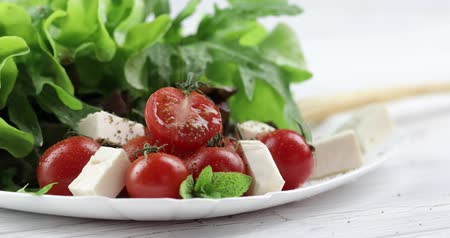 oregano : Vitamin salad from mozzarella, cherry tomatoes and lettuce. Man hands sprinkles aromatic spices