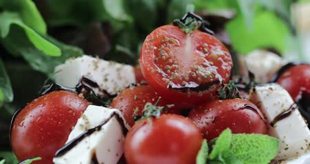 oregano : Vitamin salad from mozzarella, cherry tomatoes and lettuce is decorated with balsamic vinegar