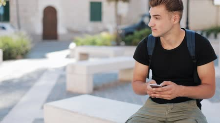 stanovena : Attractive young man with a backpack using phone sitting in old city technology busy portrait close up modern handsome smartphone ambitious mobile sunset slow motion