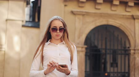 steady cam : Beautiful young business woman wearing white shirt and using smartphone while walking in the city center summer internet business outside technology eye spring mobile slow motion street happy