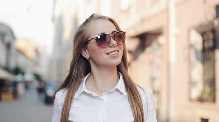 předměstí : Beautiful model with sunglasses goes through the city on foot. Looking on the outskirts of the city