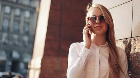 stanovena : Young business woman standing near office building at the sunny city streets and talking on a mobile cell phone. Attractive happy girl with sunglasses using cellphone outdoors, sunset