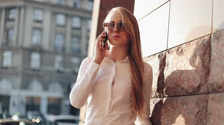motivados : Young business woman standing near office building at the sunny city streets and talking on a mobile cell phone. Attractive happy girl with sunglasses using cellphone outdoors, sunset