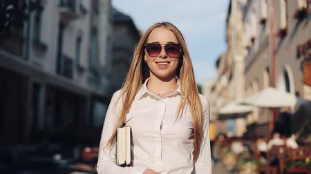 metáfora : Young attractive woman with sunglasses holding book and walk along old city. Student, education, developing, motivating, business lady