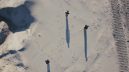 squadron : Aerial shooting. Three mens diverge on the sides in the desert. The sun throws shadows in the sand. Top view. Drug trafficking, illegal business, meeting in a neutral territory concept Stock Footage