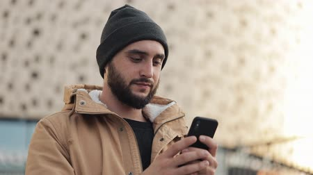 pletený : Happy young beard man using smartphone in the street near shopping mall. He is wearing an autumn jacket and knitted hat. Communication, online shopping, chat, social networking concept Dostupné videozáznamy