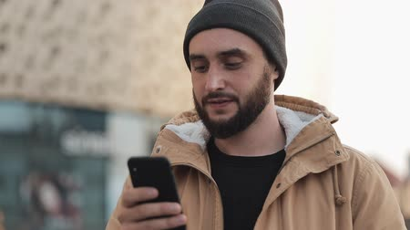 доставки : Happy young beard man using smartphone in the street near shopping mall. He is wearing an autumn jacket and knitted hat. Communication, online shopping, chat, social networking concept Стоковые видеозаписи