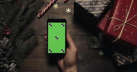 ped : Male hands tapping pages on the black smartphone with green screen. Chroma key. Top view. Vertical position. Christmas New Year concept