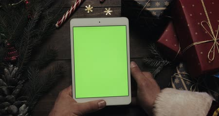 С Рождеством : Hands of Santa Claus tapping pages on the white tablet computer with green screen. Chroma key. Top view. Vertical position. Christmas New Year concept
