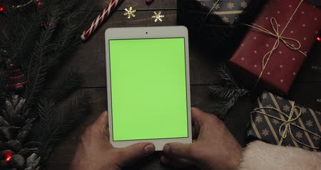 tempo de natal : Hands of Santa Claus tapping pages on the white tablet computer with green screen. Other hands placing some present boxes on the table. Chroma key. Top view. Christmas New Year internet order concept
