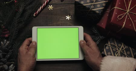 ped : Hands of Santa Claus holding white tablet computer with green screen. Other hands placing some present boxes on the table. Chroma key. Top view. Christmas New Year internet order concept