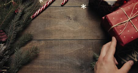 x mas : Top view of man hands tying gift box with decorating thread after wrapped with red paper on wood table, preparing for celebrating Christmas holidays at home Stock Footage