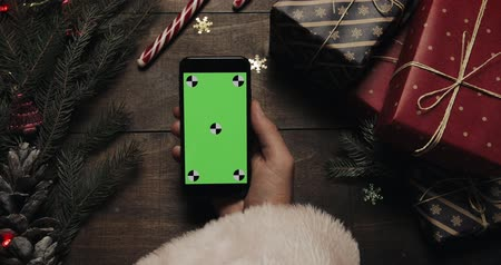 ped : Hands of Santa Claus holding black smartphone with green screen. Chroma key. Top view. Vertical position. Christmas New Year concept
