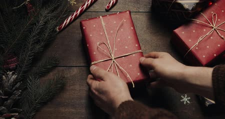 duvar kağıdı : Male hands put give big New year present on style wooden background with New year decoration and Xmas tree with blurred blinking lights. Other hands take away a gift