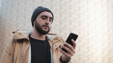 pletený : Young beard man sending audio message on cellphone at outdoor. He is wearing an autumn jacket and knitted hat. Communication, online shopping, chat, social networking concept Dostupné videozáznamy