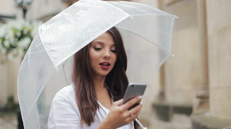 andar : Beautiful young business woman using smartphone walking on the street in rainy weather, smiling, holding umbrella. Communication concept Vídeos