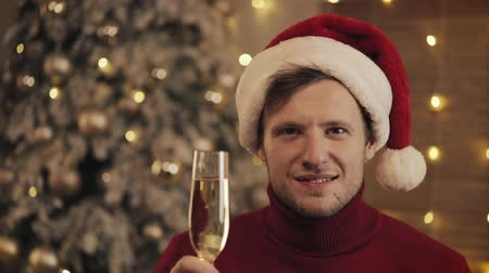 raises : Attractive Man with a Glass of Champagne in Santa Hat Looking at the Camera on Christmas Tree Background. He raises the glass. Slow motion Stock Footage