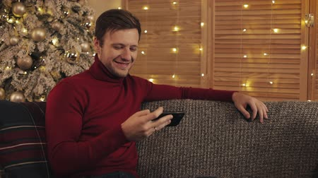 bombki : Attractive man using smartphone sitting on couch, messaging, smiling in decorated apartment near nice. He watching video on device. Christmas tree background Wideo