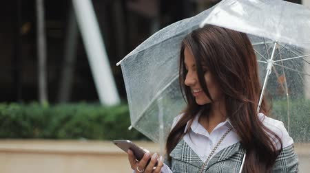 hang : Business lady in black hat with umbrella in her hand sending audio voice message on cellphone at outdoor talking to mobile assistant. Girl using smartphone voice recognition, dictates thoughts Stock mozgókép