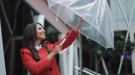 日傘 : Handsome young business woman looking up the sky and raising hand for checking if the rain stop. She smiling and close her umbrella enjoying the end of the rain 動画素材