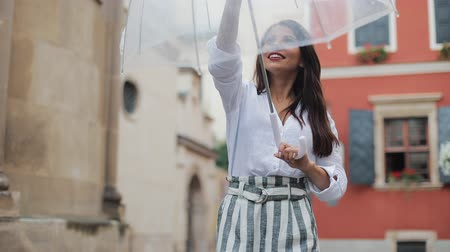 parasol : Handsome young business woman looking up the sky and raising hand for checking if the rain stop. She smiling and close her umbrella enjoying the end of the rain Stock Footage