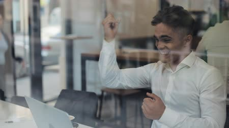 tél : Happy young business sitting at a table in a cafe working on a laptop. Winner looking at laptop showing yes gesture, celebrating success, good news on web, enjoying triumph, did it Stock mozgókép