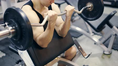 kudrlinky : Man working his arms at gym,lifting the dumbbells
