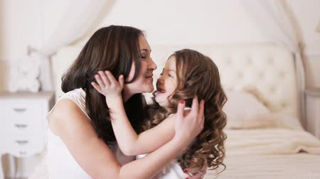 csók : little girl kissing her mother on the bed