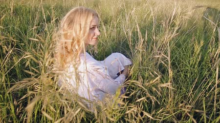 луг : girl sitting in the grass Стоковые видеозаписи