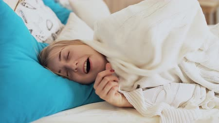 teen girl under a blanket yawning
