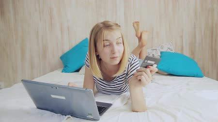 teen girl in bed with a laptop and a card. Online shopping