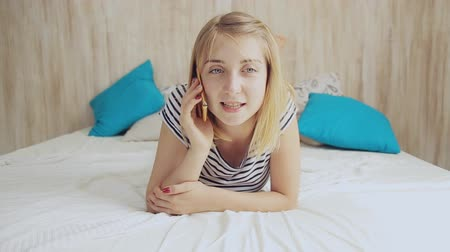 teen girl on the bed talking on the phone