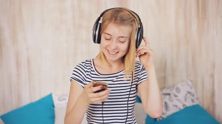 girl in headphones listening to music and shakes his head