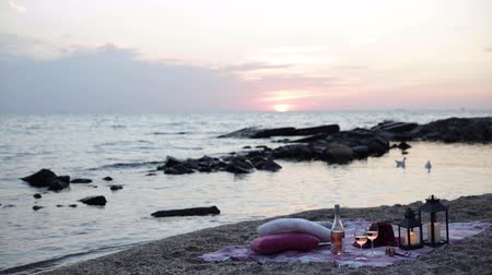 Summer sea sunset. Romantic picnic on the beach. Bottle of wine, glasses, candles, plaid and pillows. Selective focus.