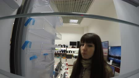 frig : Young woman is looking for a new refrigerator in an electronics store.